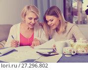 Купить «Daughter helps mother to lead home accounting», фото № 27296802, снято 13 ноября 2017 г. (c) Яков Филимонов / Фотобанк Лори