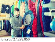 Купить «Male customer examining sleeping bags», фото № 27298850, снято 8 марта 2017 г. (c) Яков Филимонов / Фотобанк Лори