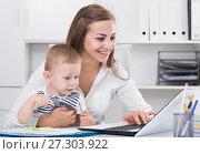 Купить «Satisfied mother with kid is productively working behind laptop», фото № 27303922, снято 13 июня 2017 г. (c) Яков Филимонов / Фотобанк Лори