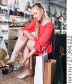 Купить «Customer woman is trying on sandals», фото № 27304222, снято 27 мая 2017 г. (c) Яков Филимонов / Фотобанк Лори