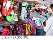 Купить «Positive man choosing alpinism cables in sports store», фото № 27305902, снято 24 февраля 2017 г. (c) Яков Филимонов / Фотобанк Лори
