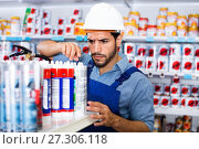 Купить «Focused workman choosing materials for renovation works in paint store», фото № 27306118, снято 13 сентября 2017 г. (c) Яков Филимонов / Фотобанк Лори