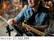 Купить «man with guitar writing to music book at studio», фото № 27322394, снято 18 августа 2016 г. (c) Syda Productions / Фотобанк Лори