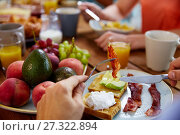 hands with bacon on fork at table full of food. Стоковое фото, фотограф Syda Productions / Фотобанк Лори