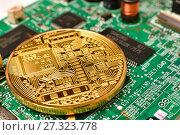 Золотая монета Bitcoin лежит на электронной компьютерной плате (2017 год). Редакционное фото, фотограф Юрий Морозов / Фотобанк Лори