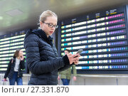 Купить «Woman in international airport checking flight information on smart phone app.», фото № 27331870, снято 21 августа 2019 г. (c) Matej Kastelic / Фотобанк Лори