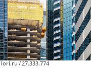 Купить «Modern building under construction, concrete floors. Facade fragment with scaffolding structures», фото № 27333774, снято 21 июля 2017 г. (c) EugeneSergeev / Фотобанк Лори
