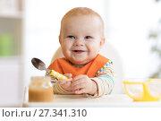 Купить «Cheerful baby child eats food itself with spoon. Portrait of happy kid boy in high-chair.», фото № 27341310, снято 24 ноября 2017 г. (c) Оксана Кузьмина / Фотобанк Лори