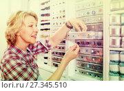 Купить «Female next to shelf with buttons», фото № 27345510, снято 23 мая 2019 г. (c) Яков Филимонов / Фотобанк Лори