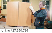 Купить «Worker carpenter is screwing fittings to cabinet at a furniture factory», видеоролик № 27350786, снято 27 марта 2019 г. (c) Константин Шишкин / Фотобанк Лори