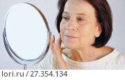 Купить «Aged woman look at her skin», видеоролик № 27354134, снято 5 января 2018 г. (c) Илья Шаматура / Фотобанк Лори