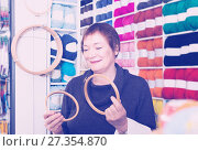 Купить «Senior woman choosing embroidery hoops for fancywork», фото № 27354870, снято 10 мая 2017 г. (c) Яков Филимонов / Фотобанк Лори