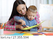 Купить «Mother helping her child to cut colored paper», фото № 27355594, снято 17 мая 2020 г. (c) Оксана Кузьмина / Фотобанк Лори