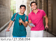 Купить «cheerful men tourists are walking with suitcases and drinking beer in unknown city», фото № 27358094, снято 19 августа 2017 г. (c) Яков Филимонов / Фотобанк Лори