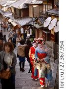 Купить «Two Maiko, Geisha apprentices, in colorful kimono walking on an old street Yasaka dori among people in Kyoto, near Kiyomizu-dera in Higashiyama, Kyoto, Japan.», фото № 27367954, снято 19 ноября 2017 г. (c) age Fotostock / Фотобанк Лори