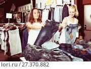 Купить «Two young girls choosing denim trousers», фото № 27370882, снято 23 октября 2018 г. (c) Яков Филимонов / Фотобанк Лори