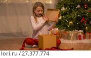Купить «happy girl opening christmas gift at home», видеоролик № 27377774, снято 27 декабря 2017 г. (c) Syda Productions / Фотобанк Лори