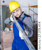 Купить «Constructor in helmet is looking at the level of the profile», фото № 27378414, снято 3 июня 2017 г. (c) Яков Филимонов / Фотобанк Лори