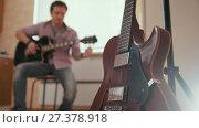 Купить «Young attractive man composes music on the guitar and plays, other musical instrument in the foreground, blurred concept», видеоролик № 27378918, снято 23 сентября 2018 г. (c) Константин Шишкин / Фотобанк Лори