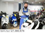 Купить «cheerful man worker displaying various motorcycles in workshop», фото № 27380874, снято 21 сентября 2019 г. (c) Яков Филимонов / Фотобанк Лори