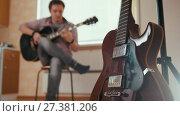 Купить «Young attractive man composes music on the guitar and plays, other musical instrument in the foreground, blurred», видеоролик № 27381206, снято 16 июля 2018 г. (c) Константин Шишкин / Фотобанк Лори