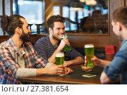Купить «male friends drinking green beer at bar or pub», фото № 27381654, снято 22 апреля 2015 г. (c) Syda Productions / Фотобанк Лори