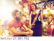 Купить «couple of musicians with guitar at music store», фото № 27381762, снято 11 декабря 2014 г. (c) Syda Productions / Фотобанк Лори