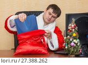 Купить «Офисный работник в костюме Деда Мороза вытаскивает из мешка с подарками папку с документами», фото № 27388262, снято 6 января 2018 г. (c) Гетманец Инна / Фотобанк Лори