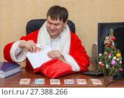 Купить «Волгоград. Россия  - 6 января 2018. Офисный работник в костюме Деда Мороза складывает деньги в конверт в подарки», фото № 27388266, снято 6 января 2018 г. (c) Гетманец Инна / Фотобанк Лори