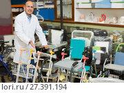 Купить «Elderly doctor posing near orthopaedic equipment», фото № 27391194, снято 24 сентября 2018 г. (c) Яков Филимонов / Фотобанк Лори