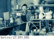 Купить «Smiling man artisan having ceramics in hands», фото № 27391390, снято 23 марта 2019 г. (c) Яков Филимонов / Фотобанк Лори