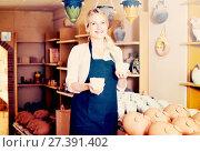 Купить «Portrait of glad woman pottery worker with ceramic crockery», фото № 27391402, снято 19 августа 2018 г. (c) Яков Филимонов / Фотобанк Лори