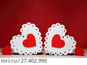 Купить «День святого Валентина, свадьба, любовь. Белые и красные яркие ажурные деревянные сердца на красном фоне с пустым местом для написания текста поздравления или приглашения.», фото № 27402990, снято 13 января 2018 г. (c) Светлана Евграфова / Фотобанк Лори