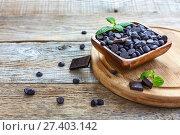Купить «Bowl with black chocolate on a wooden cutting board», фото № 27403142, снято 22 декабря 2016 г. (c) Марина Сапрунова / Фотобанк Лори