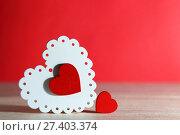 Купить «День святого Валентина, свадьба, любовь. Белые и красные яркие ажурные деревянные сердца на красном фоне с пустым местом для написания текста поздравления или приглашения.», фото № 27403374, снято 13 января 2018 г. (c) Светлана Евграфова / Фотобанк Лори