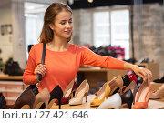 Купить «Happy young woman choosing shoes at store», фото № 27421646, снято 22 сентября 2017 г. (c) easy Fotostock / Фотобанк Лори