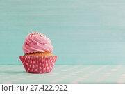Купить «pink cupcake on blue wooden background», фото № 27422922, снято 14 декабря 2017 г. (c) Майя Крученкова / Фотобанк Лори