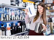 Купить «Young attractive woman choosing kettle in household appliances store», фото № 27425654, снято 12 декабря 2017 г. (c) Яков Филимонов / Фотобанк Лори