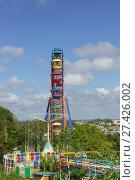 Яркое разноцветное колесо обозрения и другие аттракционы в городском парке. Стоковое фото, фотограф Наталья Гармашева / Фотобанк Лори