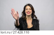 Купить «happy beautiful young woman waving hand», видеоролик № 27428110, снято 11 января 2018 г. (c) Syda Productions / Фотобанк Лори