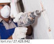 Купить «Worker renovating with drill in gloves and mask», фото № 27428842, снято 18 мая 2017 г. (c) Яков Филимонов / Фотобанк Лори