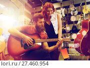 Купить «couple of musicians playing guitar at music store», фото № 27460954, снято 11 декабря 2014 г. (c) Syda Productions / Фотобанк Лори