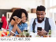 Купить «happy man and woman with smartphones at restaurant», фото № 27461306, снято 2 мая 2017 г. (c) Syda Productions / Фотобанк Лори