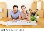 Купить «couple with boxes, blueprint and dog at new home», фото № 27461354, снято 4 июня 2017 г. (c) Syda Productions / Фотобанк Лори