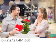 Купить «happy couple with present and flowers in mall», фото № 27461650, снято 10 ноября 2014 г. (c) Syda Productions / Фотобанк Лори