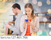 Купить «couple with smartphones and shopping bags in mall», фото № 27461766, снято 10 ноября 2014 г. (c) Syda Productions / Фотобанк Лори