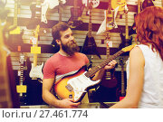 Купить «assistant showing customer guitar at music store», фото № 27461774, снято 11 декабря 2014 г. (c) Syda Productions / Фотобанк Лори