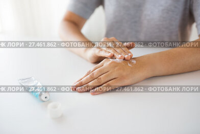 close up of hands with cream or therapeutic salve