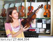 Купить «Girl choosing violin in music shop», фото № 27464394, снято 18 января 2019 г. (c) Яков Филимонов / Фотобанк Лори