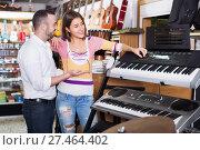 Купить «Young smiling happy couple choosing synthesizer», фото № 27464402, снято 19 августа 2018 г. (c) Яков Филимонов / Фотобанк Лори